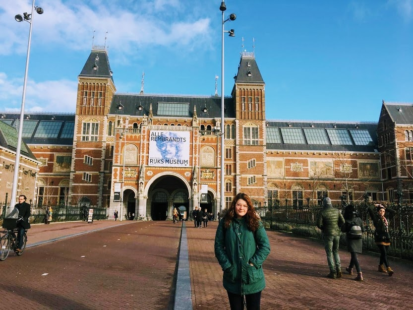 Female traveller standing in front of Rijksmuseum, the Netherlands. Exploring Europe is a 2020 goal.