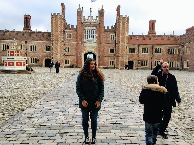 A girl who is trying to take a photo getting photobombed at Hampton Court Palace.