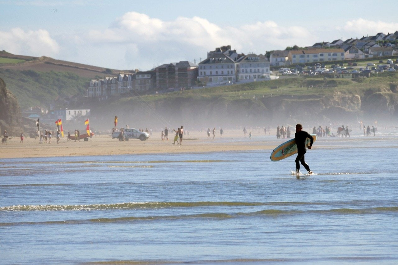 Surfer on Perranporth beach, overlooked by Perranporth accommodation